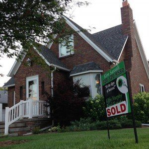"""A real estate sign proclaiming, """"SOLD"""" sits in front of a modest home."""
