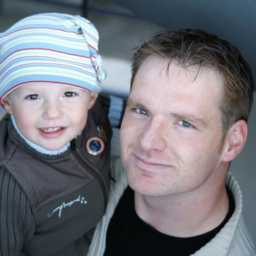 A man holds his toddler stepson, both smiling for a photograph.
