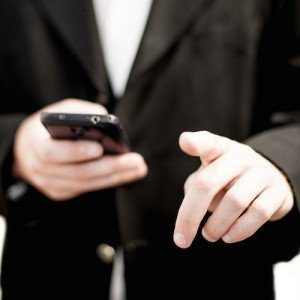 A cropped shot of a man in a business suit, focusing on his hands which hold a smartphone and gesture authoritatively.