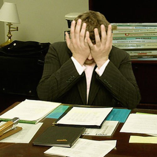 A man sits at a desk covered with papers, head in his hands, consumed by stress.