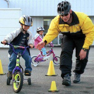 An instructor leads a child through a bicycling safety obstacle course complete with bright yellow safety cones.