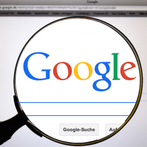 A magnifying glass inspects the home page of the popular search engine Google.