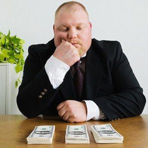 A man in a business suit frowns thoughtfully at three stacks of cash on the table in front of him.