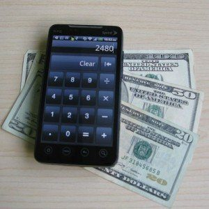 A smartphone displaying a calculator app, resting on three fanned-out cash bills adding up to $170.