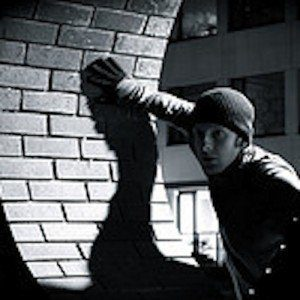 Black and white photo of a burglar in a stocking cap lurking in the shadows of an alley.