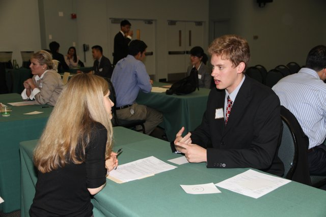 A young prospective employee asks questions across the table at a job fair.