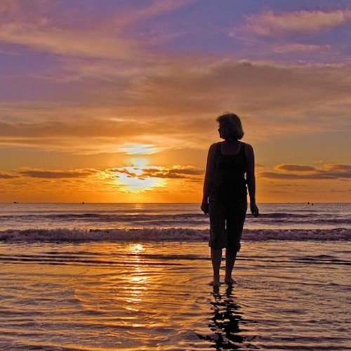 A woman silhouetted by the orange and purplesunset walking on the beach.