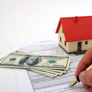 A hand signs an official document, as a pile of one-hundred dollar bills and a model of a house looks on.