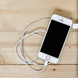 A white iPhone plugged into a USB port.