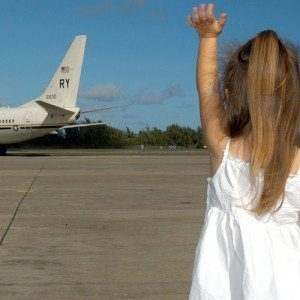 A young girl faces away from the camera, standing on the tarmac and waving goodbye to an airplane.