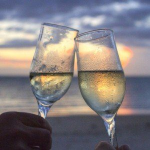 Two glasses of champagne clinking together on a beach at sunset.
