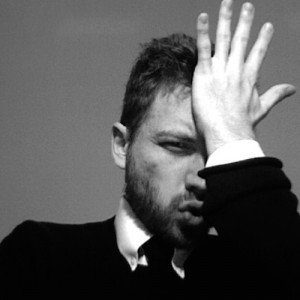 A black and white photo of a man dressed in a suit smacks his palm to his forehead in frustration.