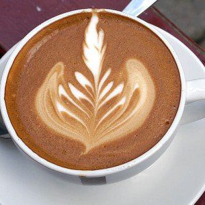 A leaf-like design made from milk and foam in a latte from a coffee shop.