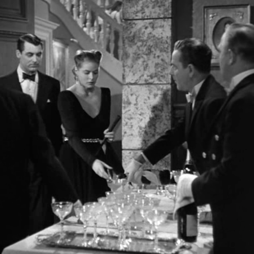 A still image from the film Notorious showcasing an awkward conversation full of suspicion at a dinner party.