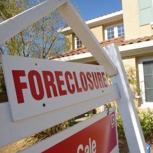"A white and red ""Foreclosure"" sign in front of a house."