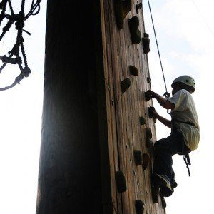 A teenager reaches the summit as he climbs a rock wall.