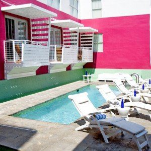 Poolside at a Florida retirement home - hot pink walls, bright blue water, and white cabanas in paradise.