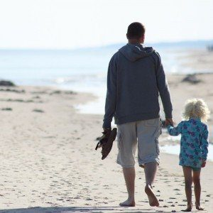 A man and a young girl walk hand in hand facing the ocean, carrying their shoes as the walk in the sand.