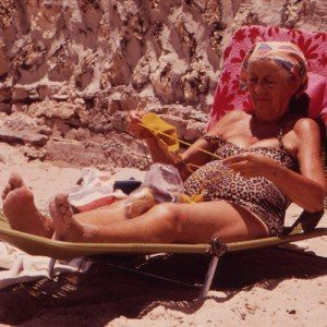 A retired woman lounges, sunbathing on the beach.