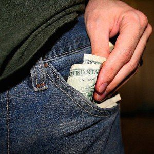 A wad of cash being placed into the pocket of a pair of blue jeans.