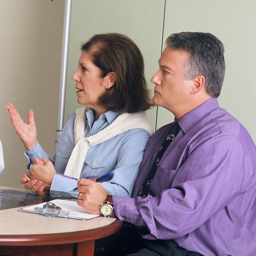 A man and woman sit at a desk, discussing a matter of importance with an unseen authority figure.