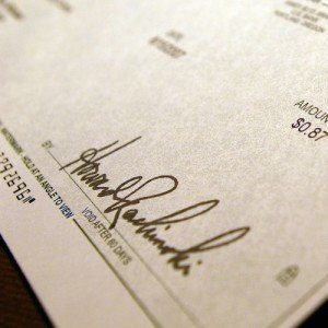 A bold and precise ink signature on a personal check.