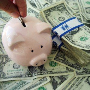 A hand puts coins in a piggy bank atop a large pile of dollars.