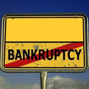 "A yellow sign declaring ""Bankruptcy"" with a red line through it."
