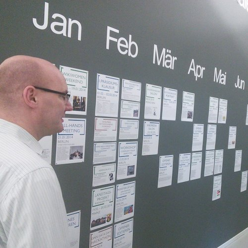 A man surveys a wall used solely as a calendar.