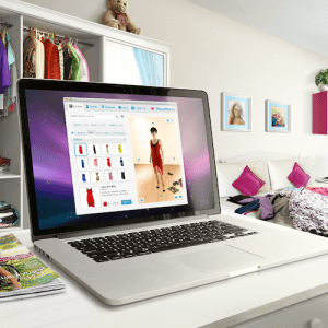 An open laptop, displaying a website for online clothes shopping, on a desk in a trendy young woman's room.