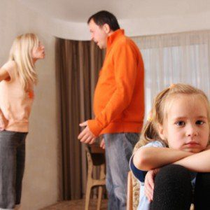 Two parents argue in the background of the photo, shouting at each other, while a sad child sits turned away from them in the foreground.