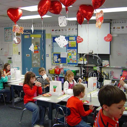A Valentine's Day celebration in an elementary school. Red, heart-shaped balloons hover over each desk, and children give out paper Valentines to their classmates.