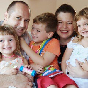 A happy family of three children and their parents, huddling close and smiling for a photo.