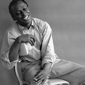 Black and white photo of jazz musician Miles Davis, candidly smiling and laughing.