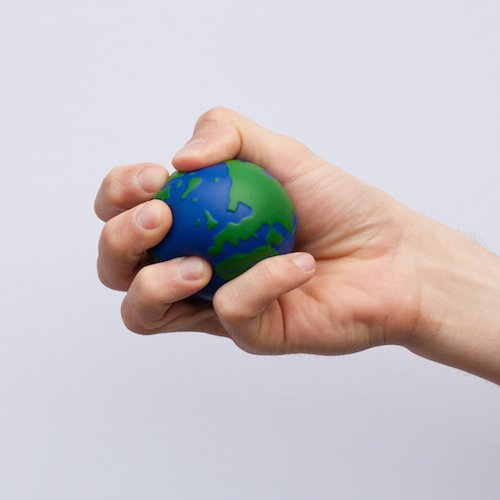 A hand squeezing a stress ball, painted blue and green to look like the Earth.