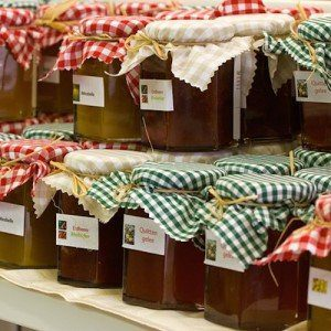 Rows of canned jams with informative labels and festive green, red, and white gingham cloth lids.