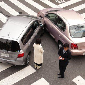 A man and woman stand by their respective cars, surveying the damage of their auto accident.