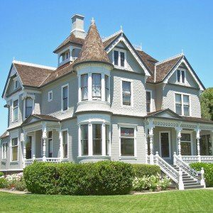 A stately Victorian-style home, painted white with brown roofs, on an impeccably manicured lawn.