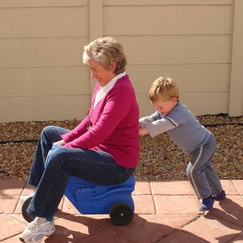 A young boy helping push his grandmother on a toy vehicle.