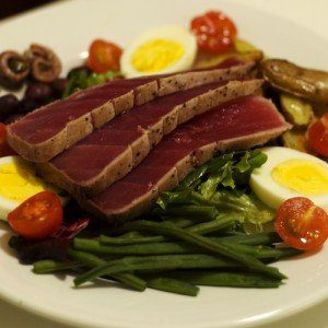 Grilled steak strips atop a salad of greens, green beans, cherry tomatoes, and hard boiled eggs.