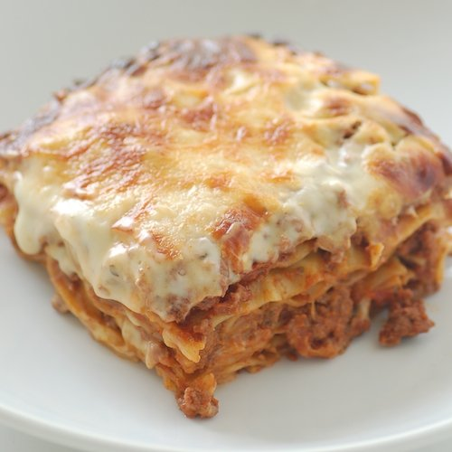 A generous portion of cheesy lasagna on a white plate..