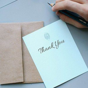 A hand holding a pencil hovers over a light blue thank you card with a recycled-paper envelope.