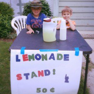 Children sit at a homemade lemonade stand.