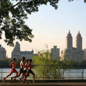 A group of runners pass the Manhattan skyline in central park.
