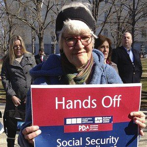 "A woman at a rally holds a sign reading, ""Hands Off my Social Security."""