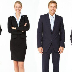 A man and woman pose in respectable business attire.