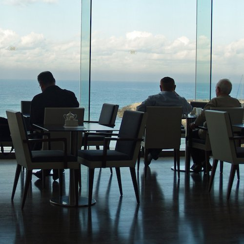 Men on a business trip sit in front of bay windows with a waterfront view, silhouetted.