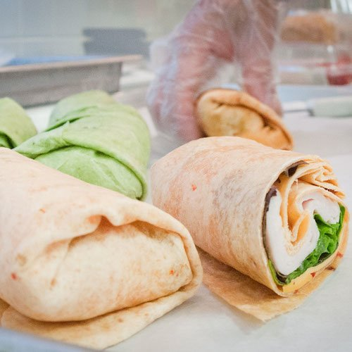 A chef prepares smoked turkey wraps, combining lettuce, cheese, and smoked turkey, wrapped up in a tortilla.