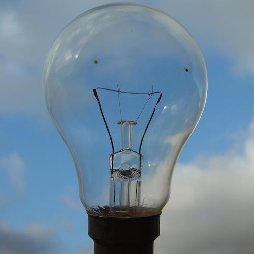 An unlit lightbulb held up against a background of blue sky and fluffy, white clouds.