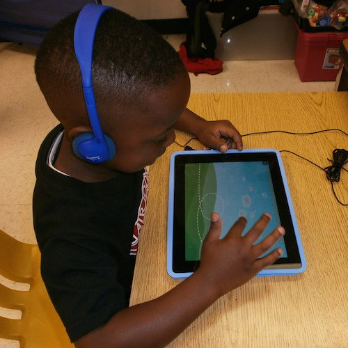 A child sits at a desk, headphones on, playing a game on a tablet.